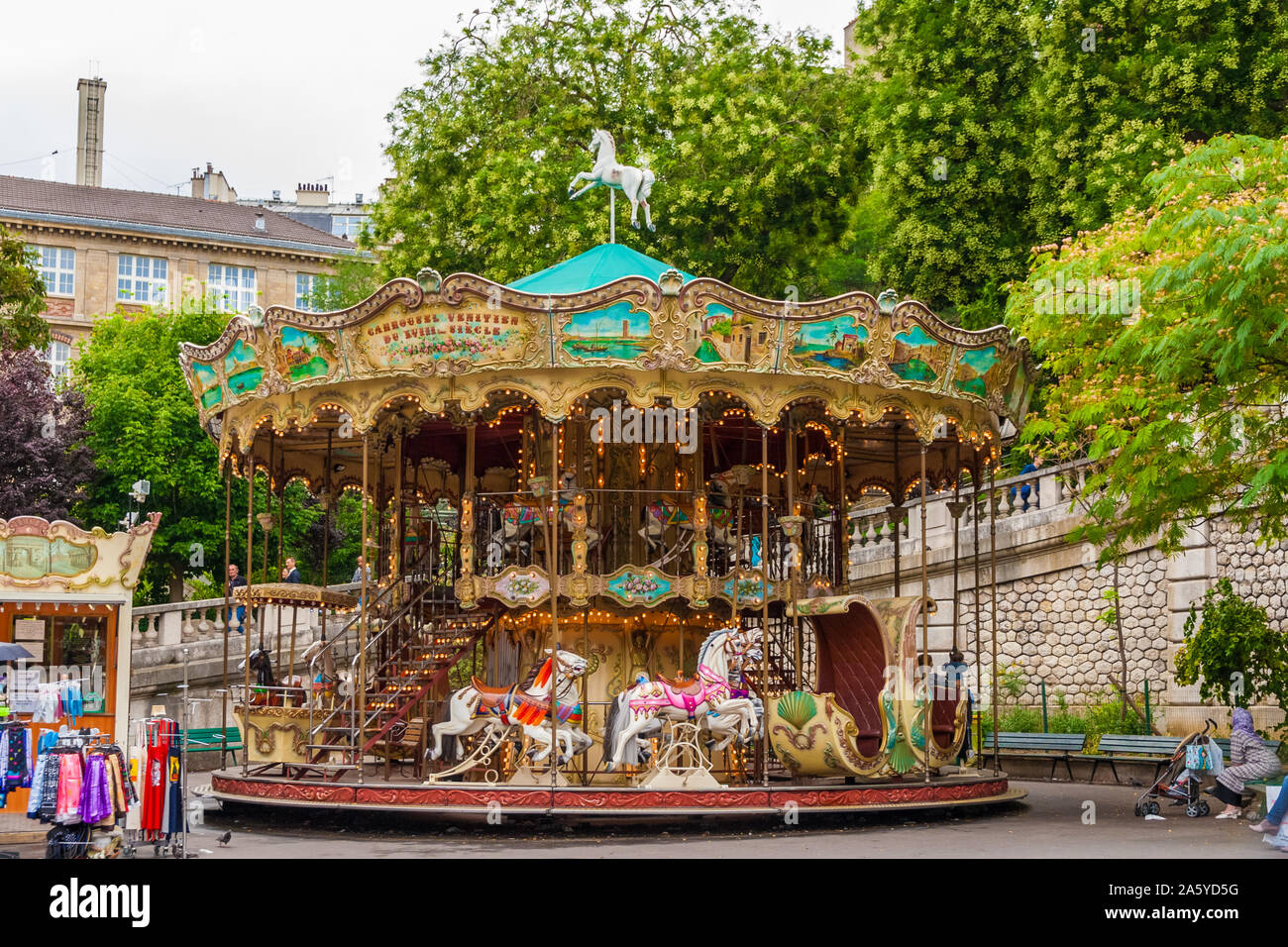 A lovely French old-fashioned style carousel with rows of wooden horses mounted on posts and a staircase to the second floor in the Louise Michel... Stock Photo