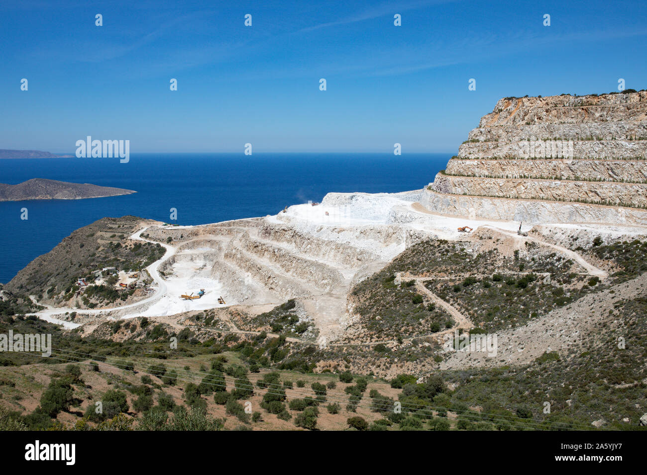Crete landscape, blue sea and sky on a sunny day. A Quarry - rocks and green hills. Stock Photo