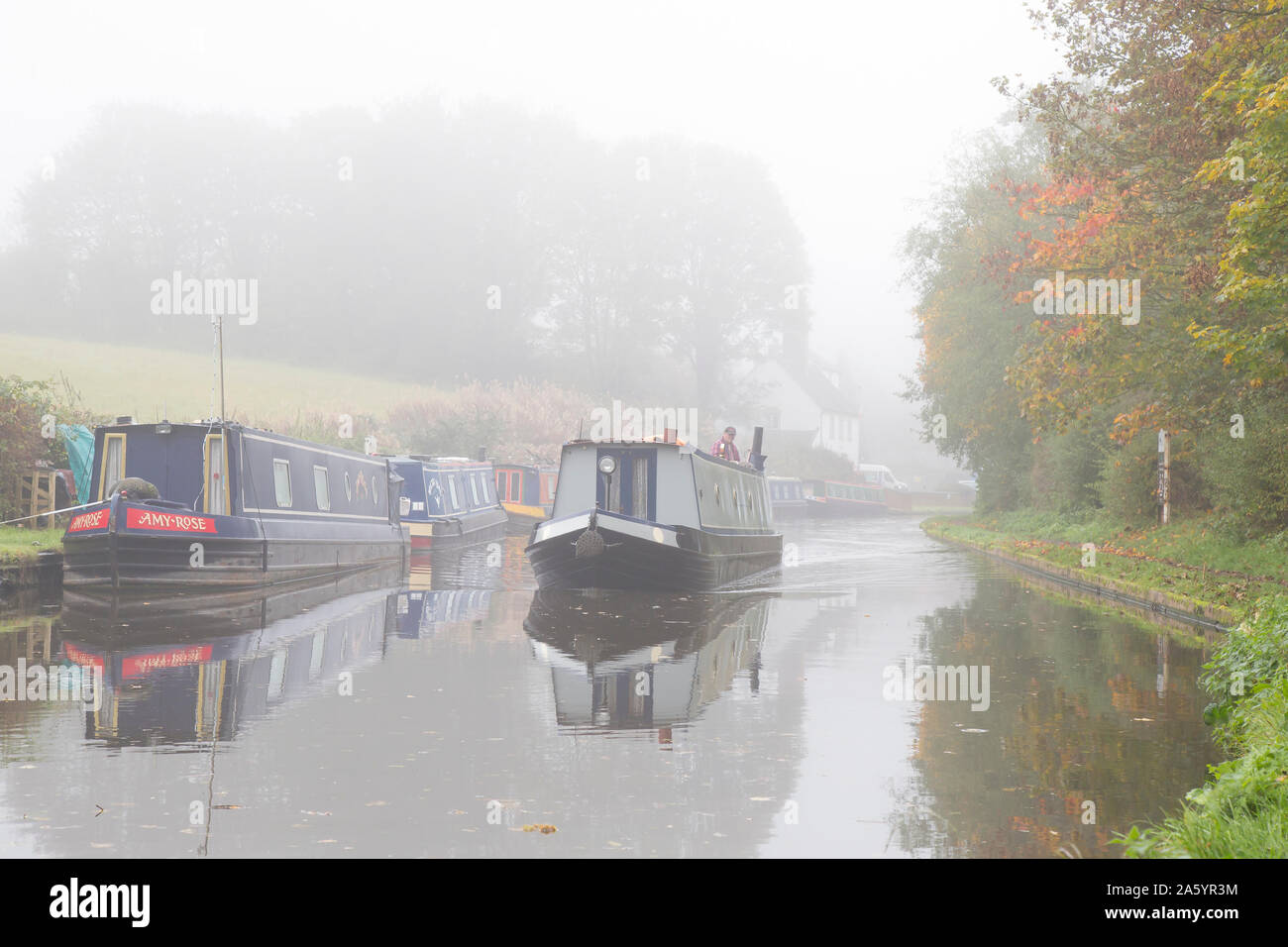 Stourbridge, UK. 23rd October, 2019. UK weather: heavy fog slows down traffic for commuters today, although some travellers are used to the slow speed of commuting as we see a UK narrowboat making its way in the 'slow' lane of a british canal, moving slowly through the early  morning mist. Credit: Lee Hudson/Alamy Live News Stock Photo