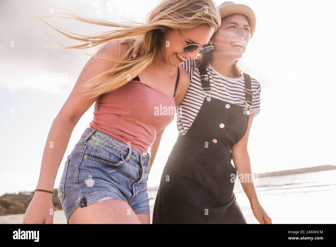 Two girlfriends having fun, walking on the beach Stock Photo