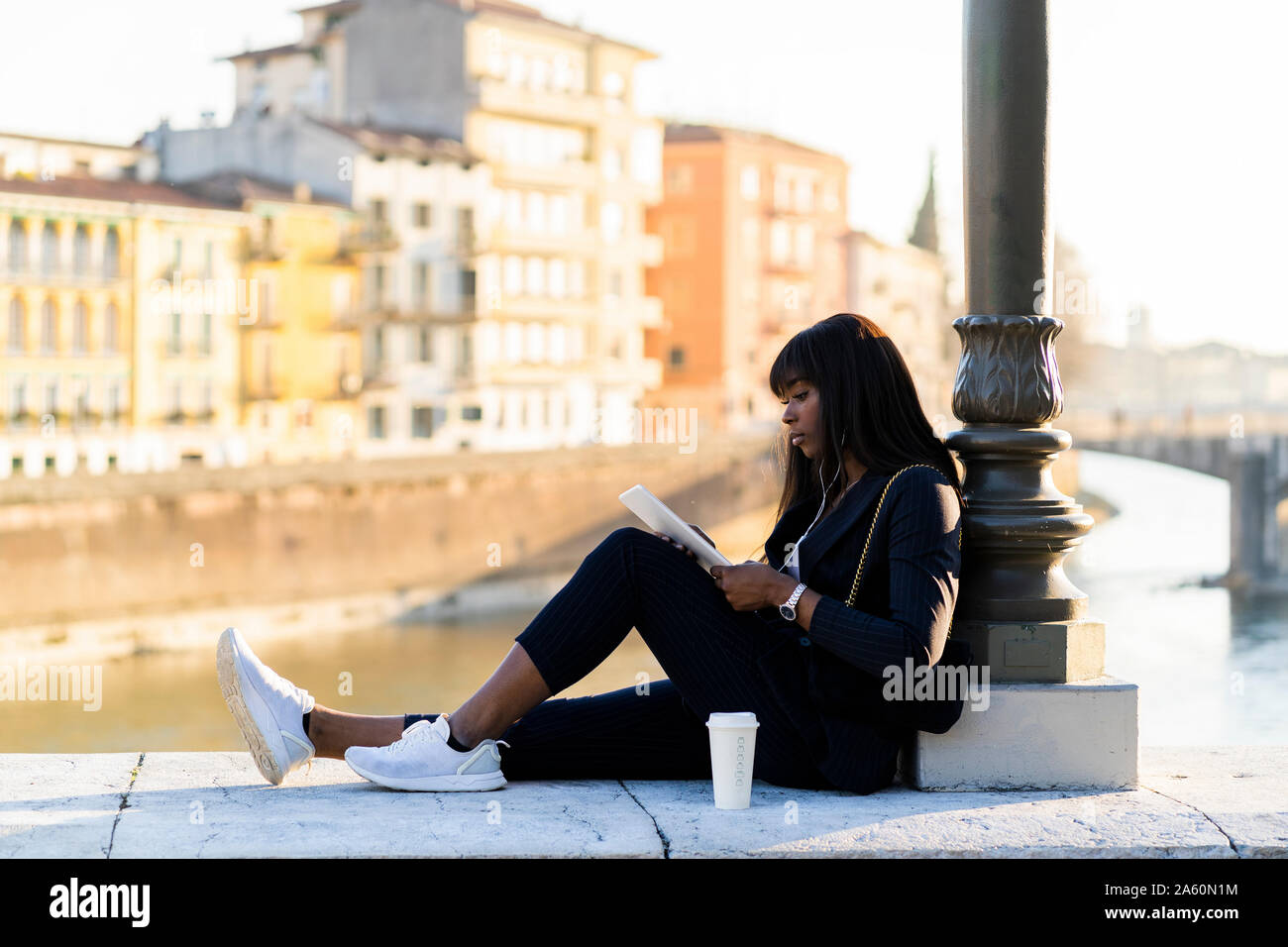 Businesswoman sitting outdoors using a digital tablet Stock Photo