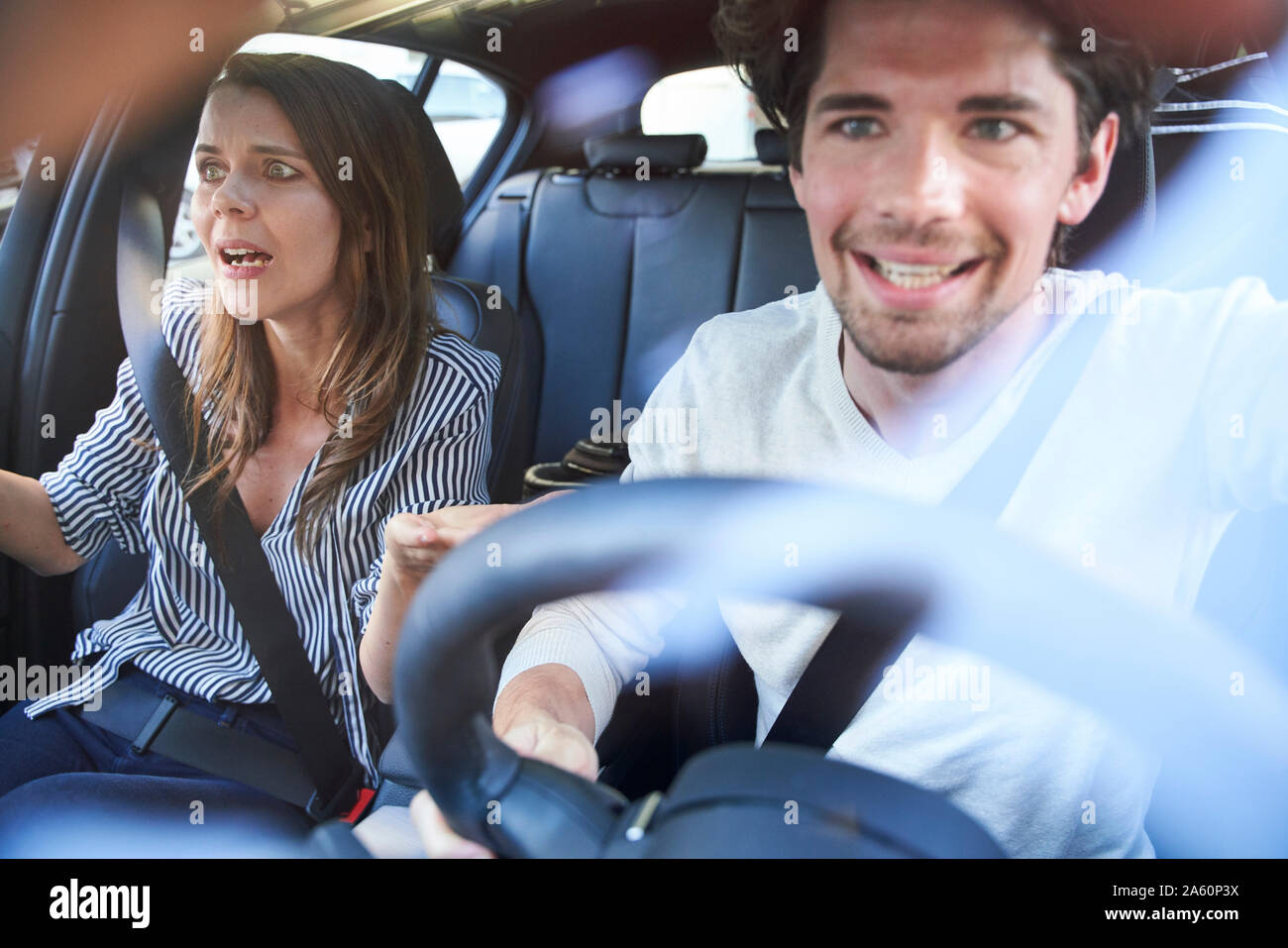 Shocked couple in a car with man driving Stock Photo
