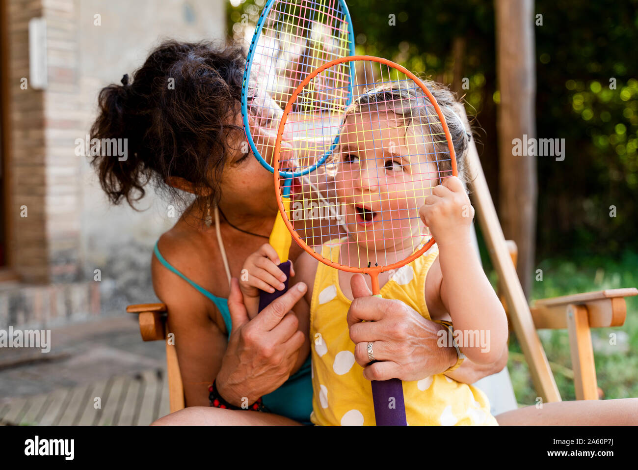 Grandmother playing with little girl and badminton rackets outdoors Stock Photo