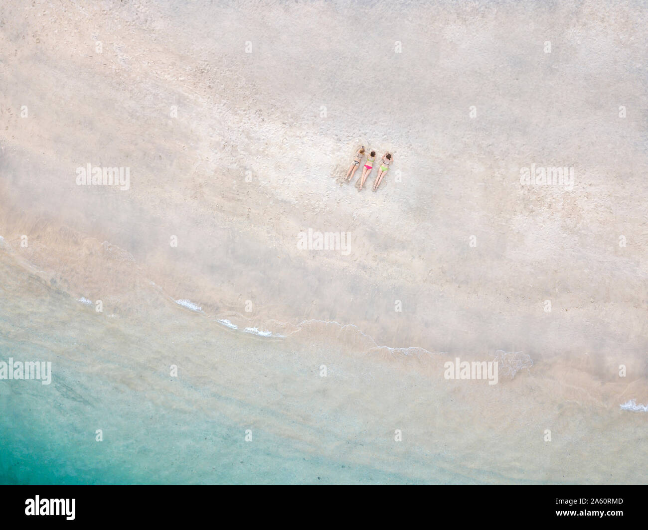 Aerial view of young women lying at the beach, Gili Air island, Bali, Indonesia Stock Photo