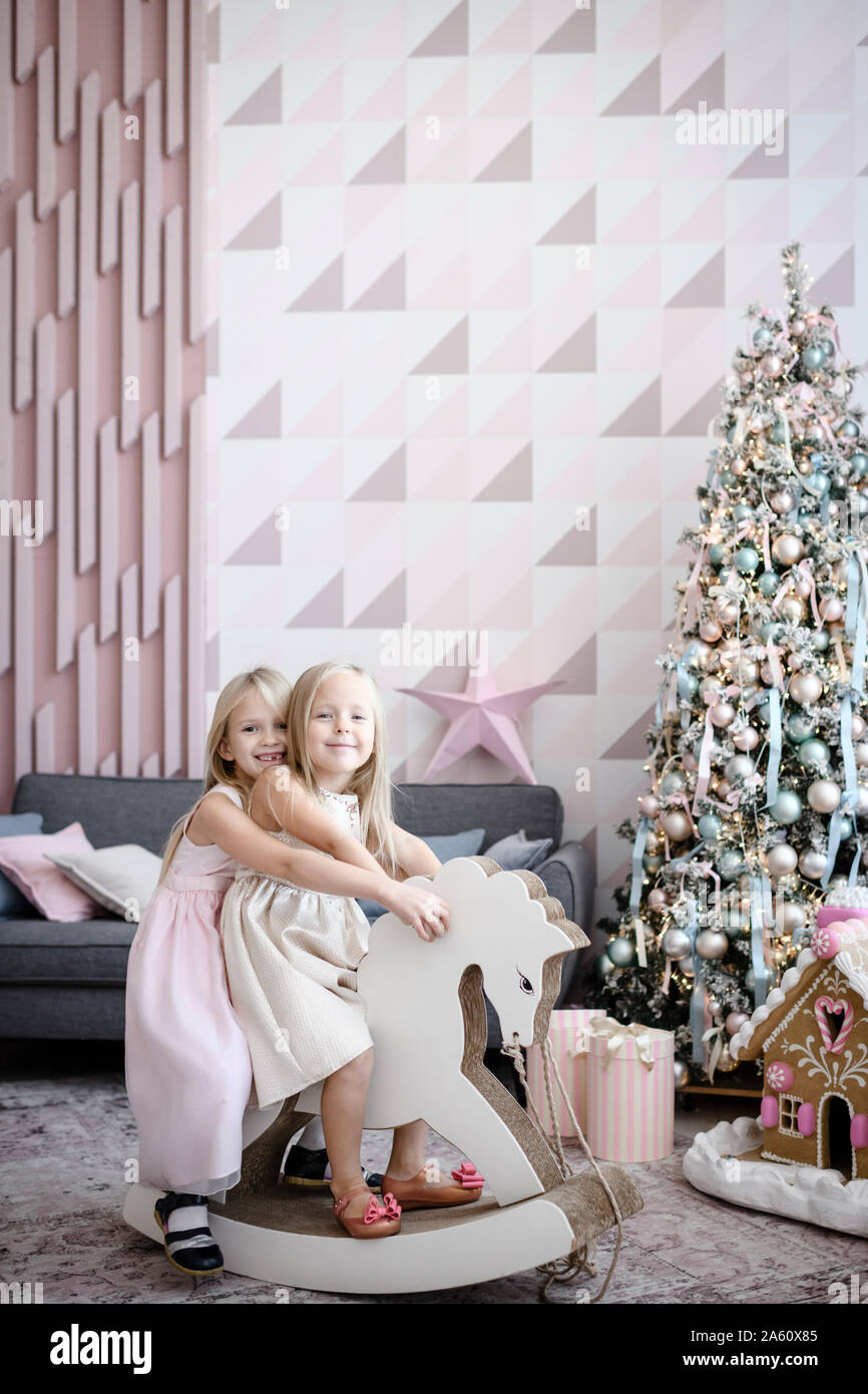 Portrait Of Happy Two Little Girls Together On A Rocking Horse At Christmas Time Stock Photo Alamy