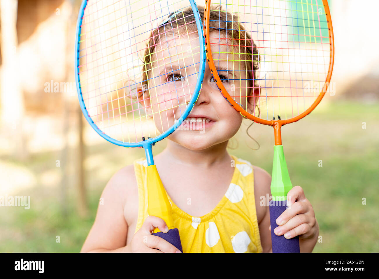Little girl playing with colorful badminton rackets outdoors in summer Stock Photo