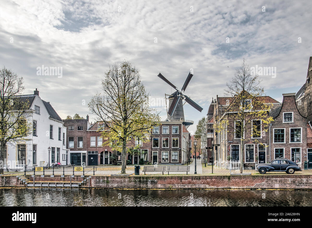 Schiedam, The Netherlands, October 23, 2019: view across the Long Harbour towards Fish Market square, with a windmill, old lanterns and houses and an Stock Photo