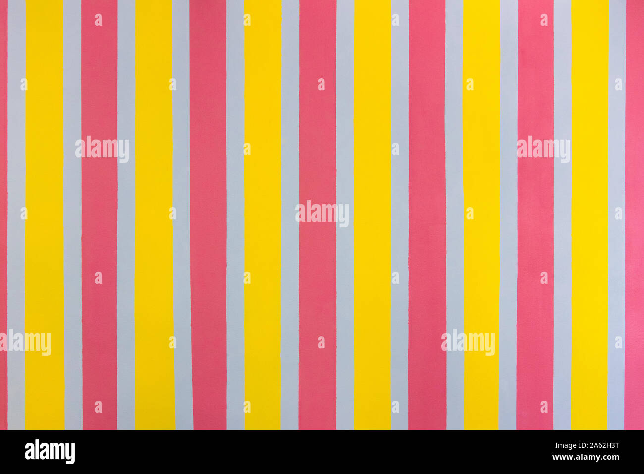 Bright rough wall painted in stripes. Striped seamless pattern with vertical stripes of pink, gray and yellow. Stock Photo