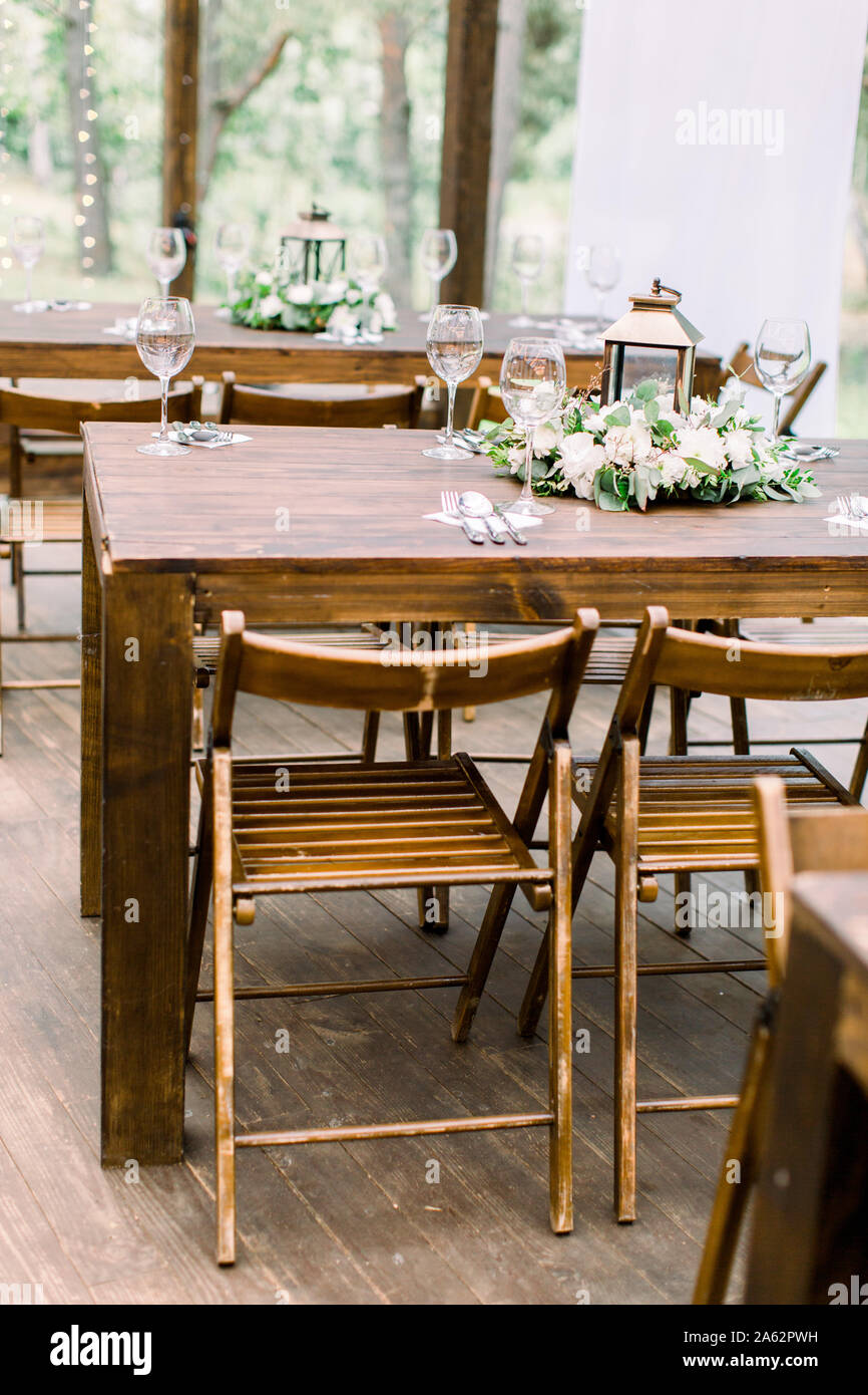 Wedding Rustic Style Wedding Table Decoration Wooden Table Decorated By Knives And Forks Wineglasses Greenery And Flowers With Golden Lantern Stock Photo Alamy