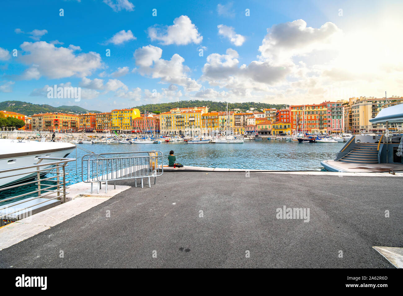 A woman eats her lunch alone along the dock at the colorful old port of the Mediterranean city of Nice, France, along the French Riviera. Stock Photo