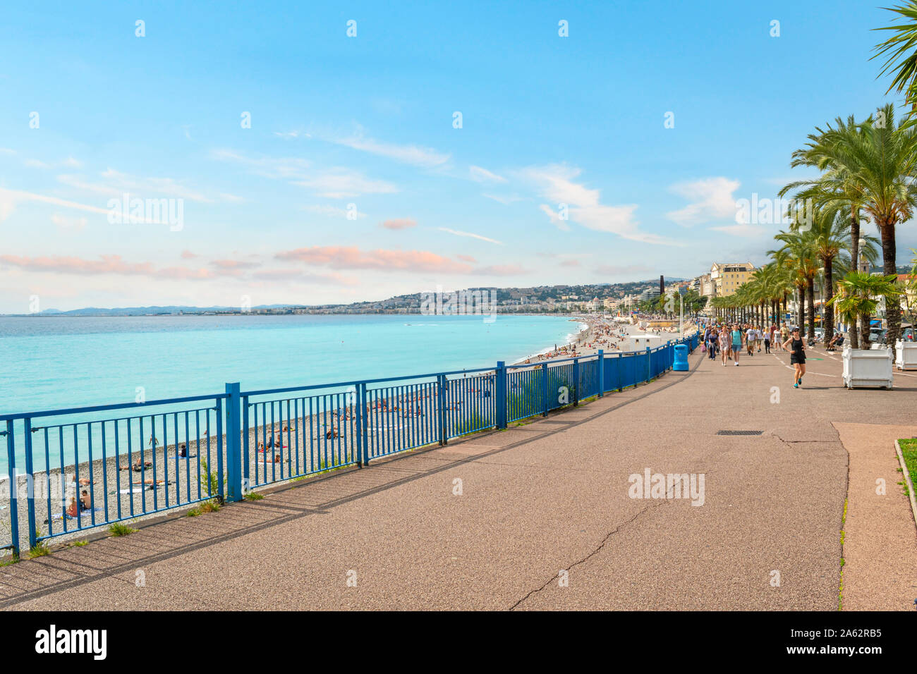 Joggers and walkers pass the Mediterranean sea and beach along the Promenade des Anglais on the French Riviera in Nice France Stock Photo