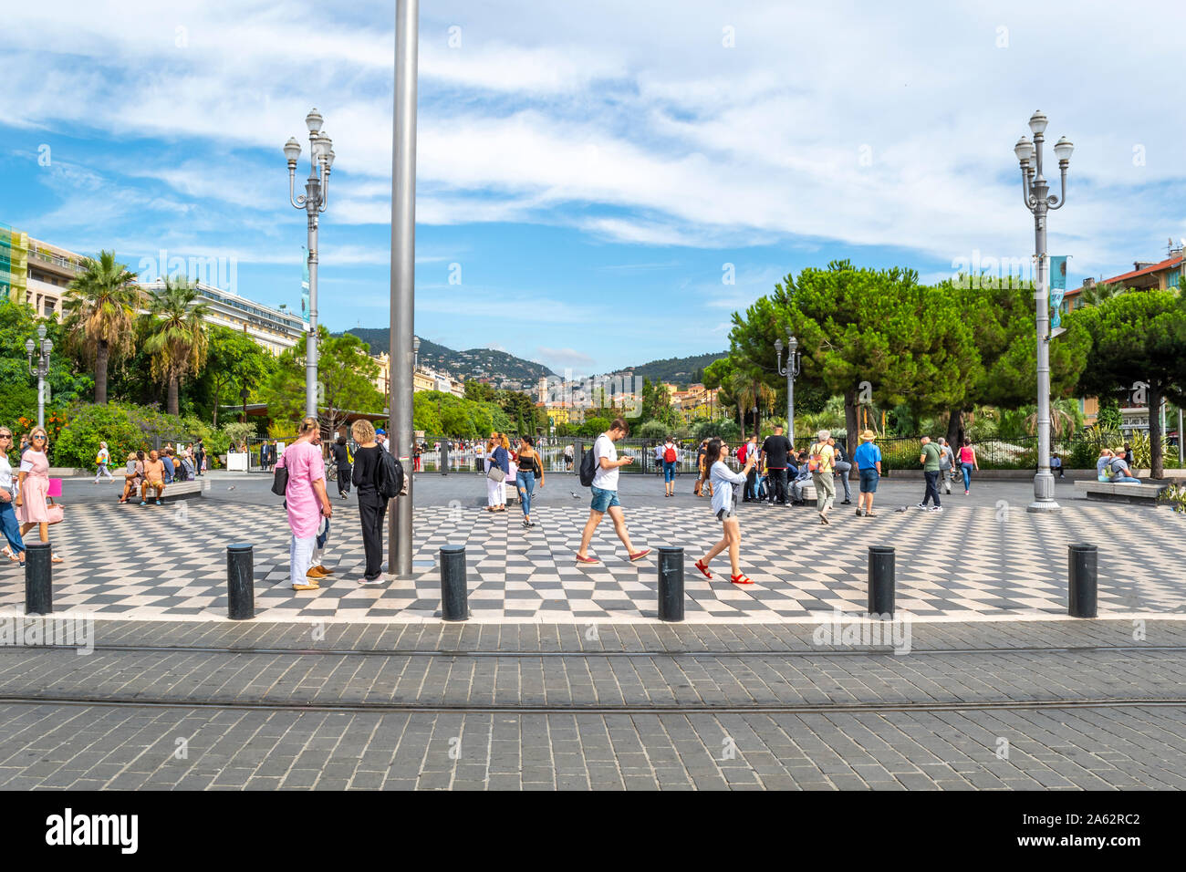 Tourists enjoy a pleasant day on the French Riviera as they stroll Place Massena with Promenade du Paillon water park in the distance in Nice France Stock Photo