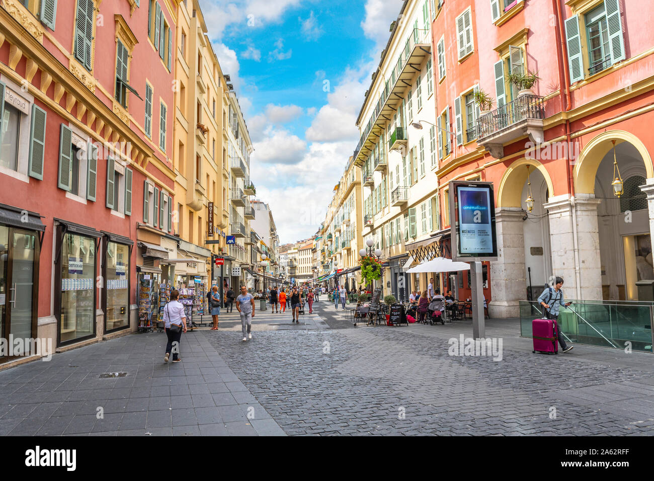Tourists shop and dine at cafes along one of the main streets near Old Town Nice, in the Mediterranean city of Nice, France. Stock Photo