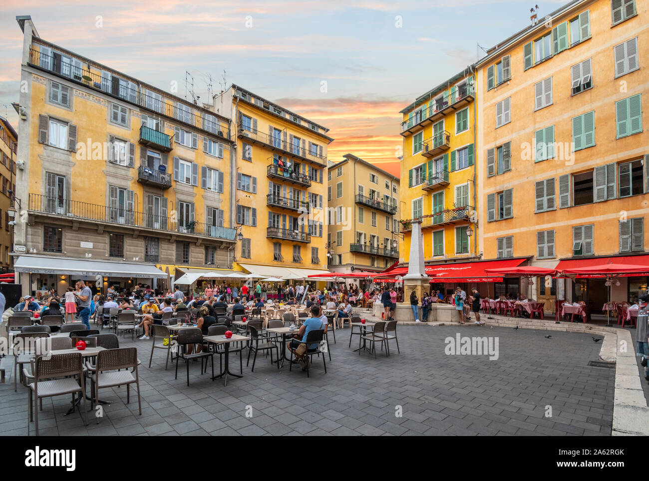 Tourists and locals enjoy an early evening at the cafes, the water fountain, and shops in Place Rossetti, one of the main piazzas in Vieux Nice France Stock Photo