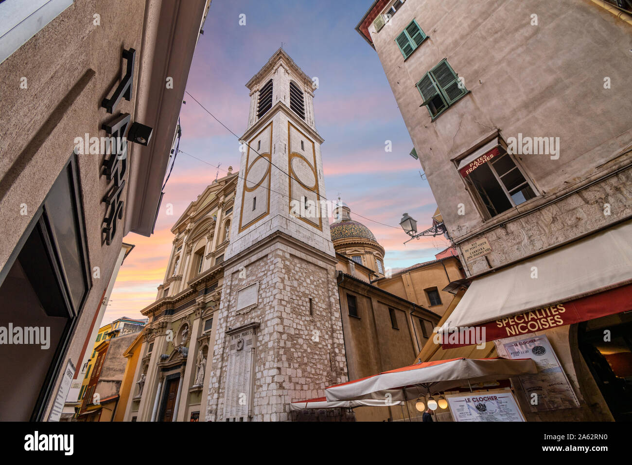 View of the campanile bell tower and the Nice Cathedral at Place Rossetti past an apartment building as the sun sets in Old Town Nice France. Stock Photo