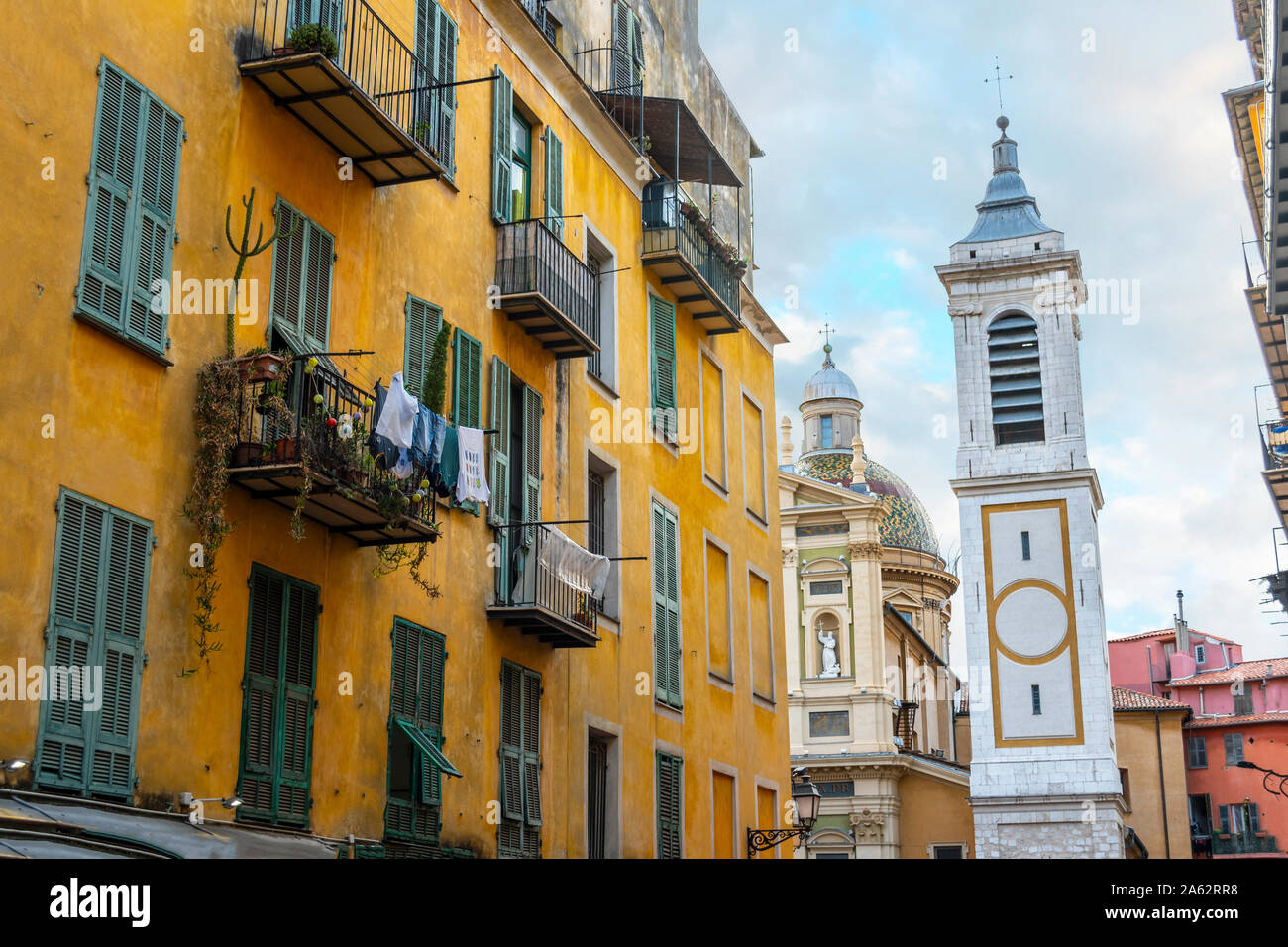 View of the campanile bell tower of the Nice Cathedral at Place Rossetti past an apartment building with laundry hanging in Old Town Nice France. Stock Photo