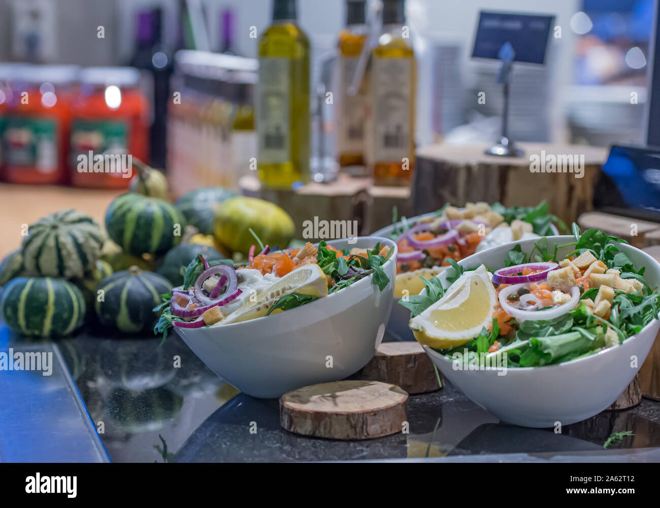 salad bar with bowls with onions and lemon rucola and pumpkin in the background as well as olive oil and other sauces Stock Photo