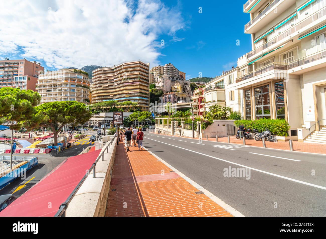 Pedestrians walk the Grand Prix street circuit near St Devote in Monte Carlo, Monaco. Stock Photo