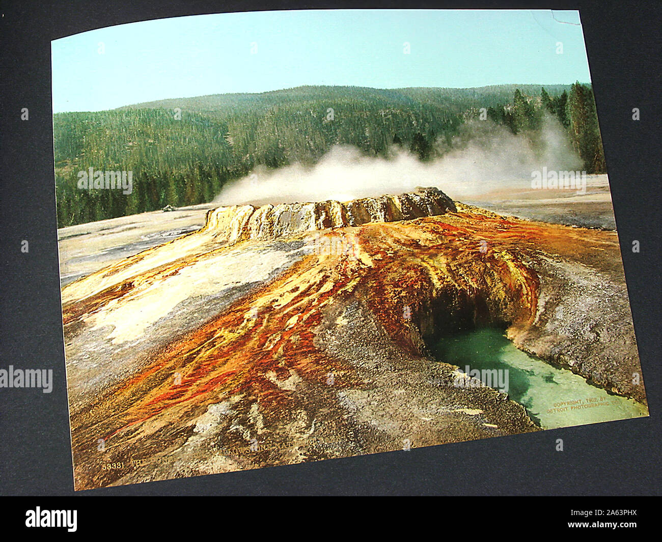 Nice and vintage album containing early Photochrom style colorized photographs of Yellowstone National Park. Stock Photo