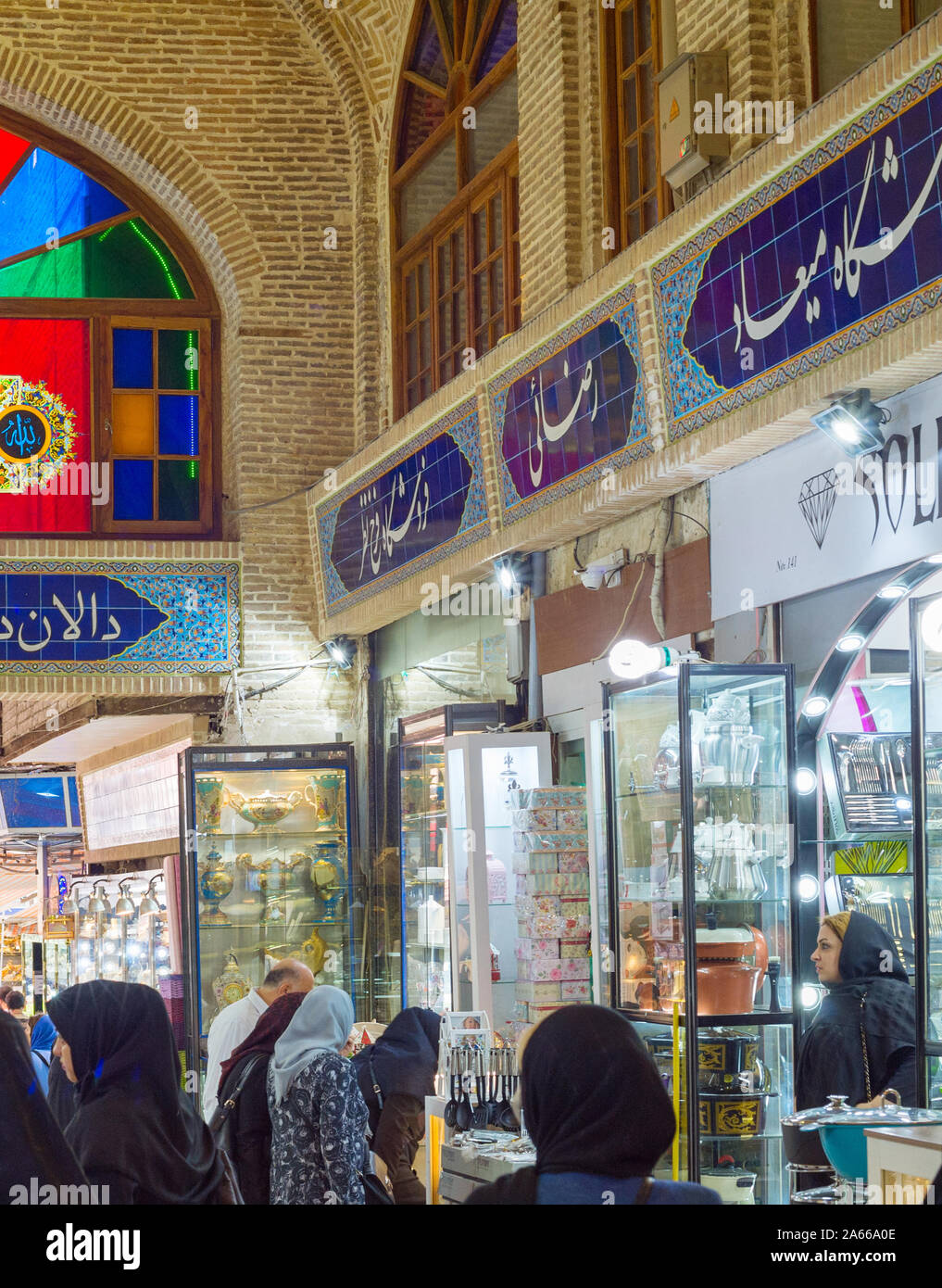 TEHRAN, IRAN - MAY 22, 2017: Crowd of people in row of Grand Bazaar with stalls of dishes Stock Photo