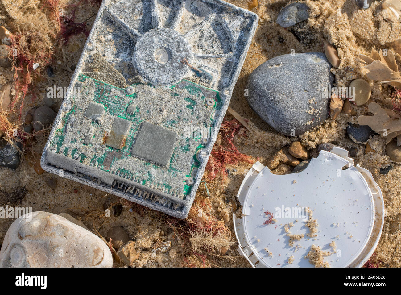 Computer pollution. Washed-up obsolete technology causing waste management problem. Marine toxic hazard and land-fill disaster as changing tech has en Stock Photo