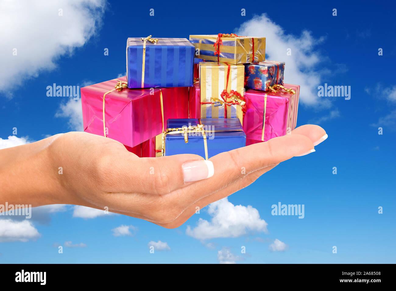 Hand mit Geschenke, Pakete, Päckchen, Weihnachtsgeschenke, Weihnachten, bunt eingepackte, Stock Photo