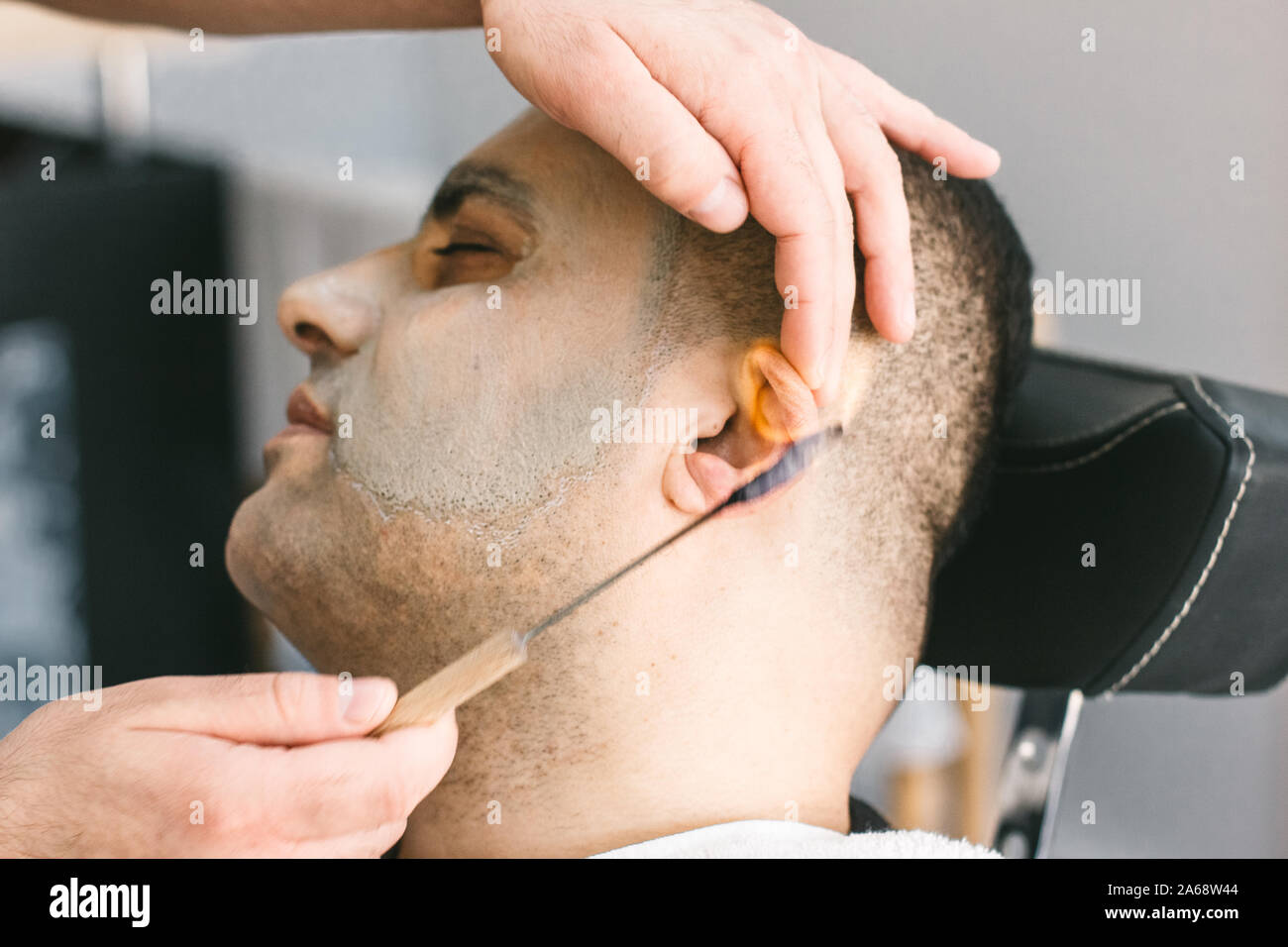 Hairdresser removes hair from the ears of man in a barber shop by burning fire. Stock Photo