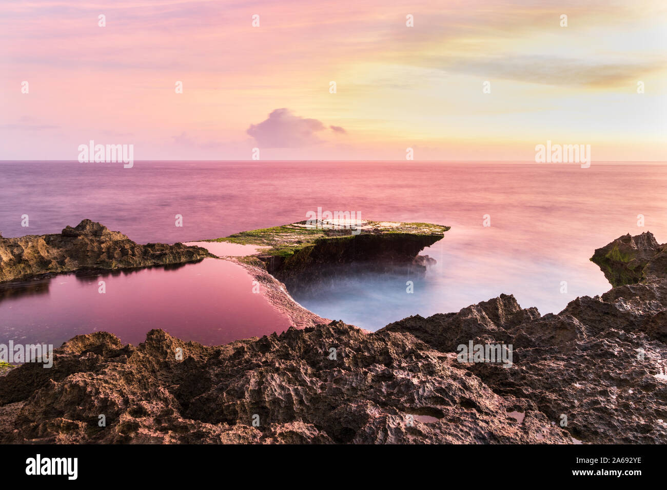Devil's Tear at sunset, island of Nusa Lembongan, Bali, Indonesia. Rocky shore in foreground. Tidepool and ocean pink from setting sun's reflection. Stock Photo