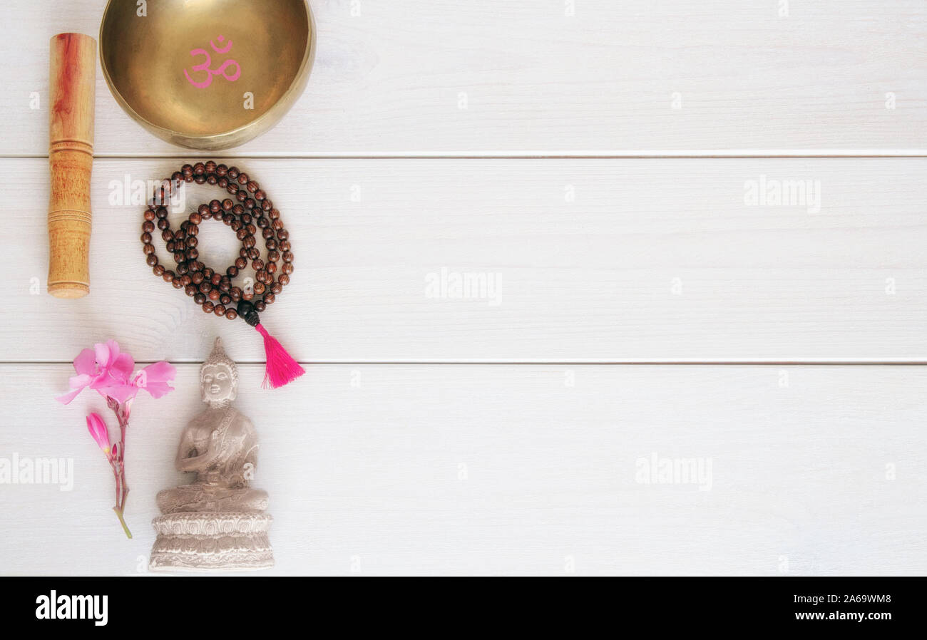 Meditation or mindfulness concept. Wooden mala beads, tibetan singing Bowl with symbol OM  and Buddha statue with flower on wooden background with cop Stock Photo