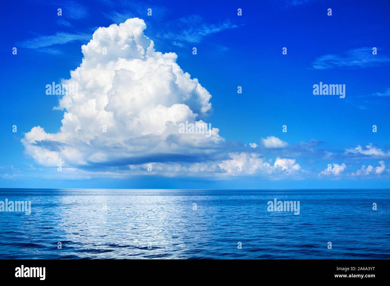 White cumulus clouds in blue sky over sea landscape, big cloud above ocean water panorama, beautiful tropical seascape, cloudy weather, cloudscape Stock Photo
