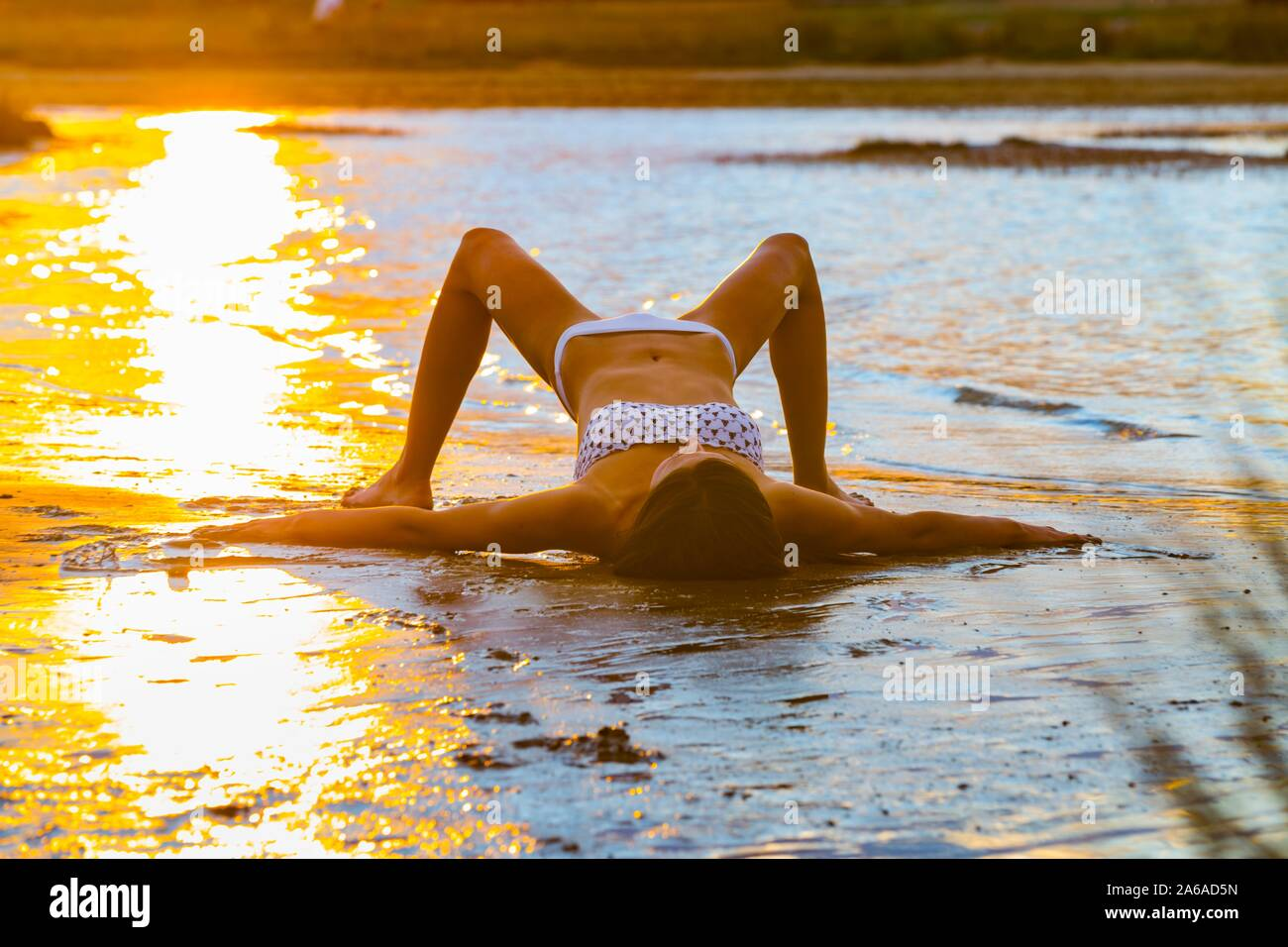 Overstretched on beach in sunset time late day spreading arms and legs in shallow water sea Stock Photo