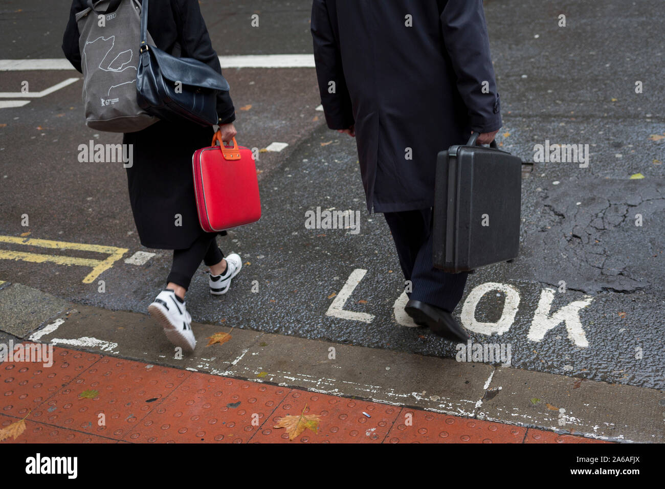 After heavy rainfall, Londoners and visitors cross Kingsway, on 24th October 2019, in Westminster, London, England. Stock Photo