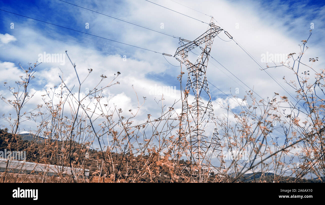 Electrical tower against a cloud blue sky. Renewable and clean energy concept with empty copy space for Editor's text. Stock Photo
