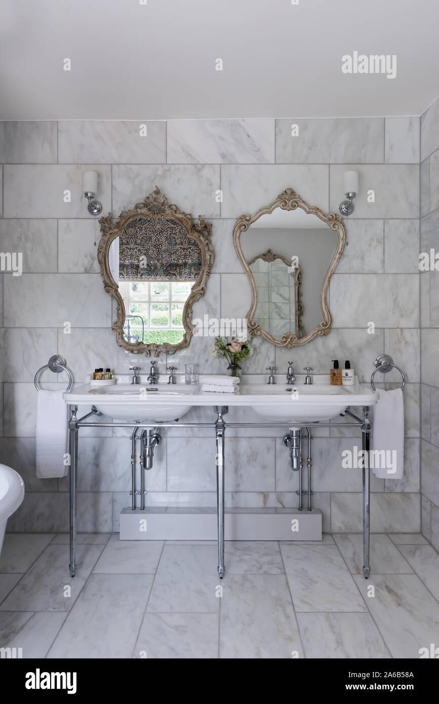 1930s Art Deco Style Decorative Mirrors Above Double Washbasin In Marble Bathroom Stock Photo Alamy