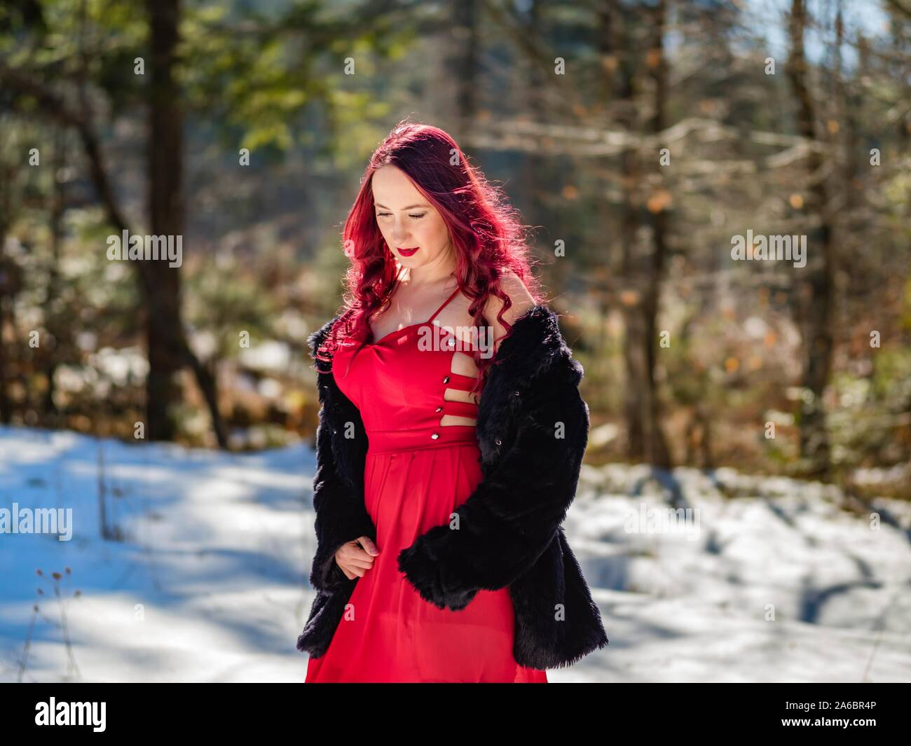 Young woman on snow dressed fancifully is walking on snow in forest Stock Photo