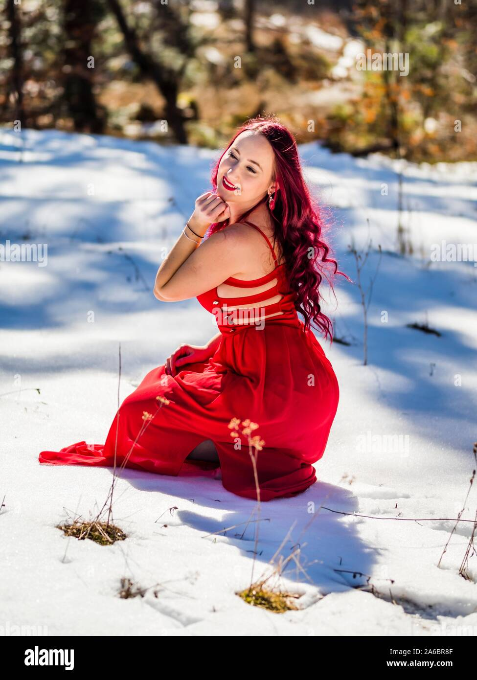 Young woman on snow squatting dressed fancifully looking towards camera smiling Stock Photo