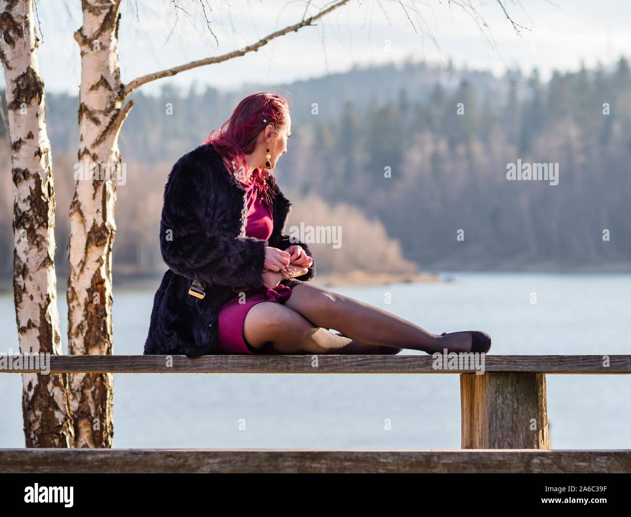 Leisurly seated on wooden bench looking away into distance background Stock Photo