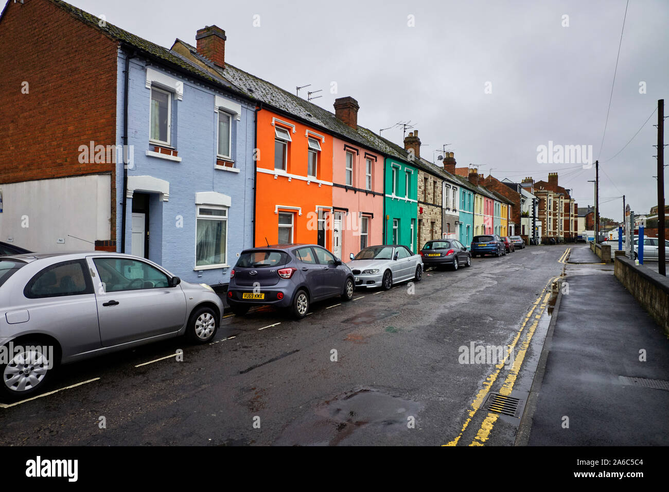Row of brightly painted terraced houses in Nettleton Road, Gloucester all painted different colours Stock Photo