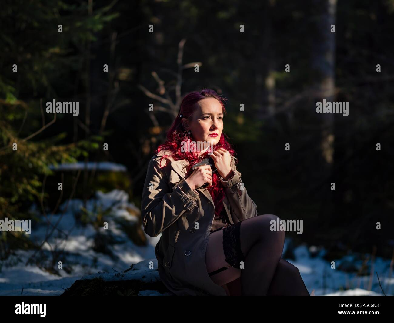 Sexy young woman on snow dressed fancifully sitting seated in dark evergreen forest lit lighted by sun sunburst Stock Photo