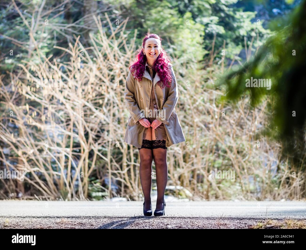 Buttoning her coat standing on country-road smiling looking at camera Stock Photo