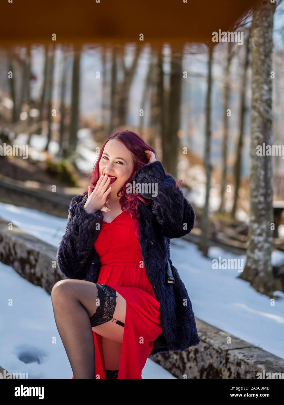 Exposing leg thigh nylon Black stockings with suspenders slitted Red long dress Black Winter coat smiling shy looking at camera hand cover mouth Stock Photo