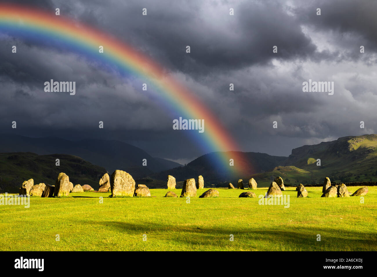 Rainbow over Castlerigg Stone Circle on summer solstice eve with sun and dark clouds in Cumbrian Mountains Lake District Keswick England Stock Photo