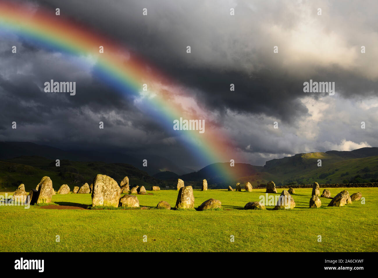 Rainbow over Castlerigg Stone Circle on summer solstice eve with sun and dark clouds over Cumbrian Mountains in Lake District Keswick England Stock Photo