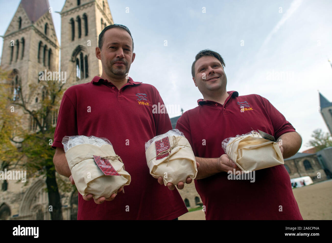 24 October 2019, Saxony-Anhalt, Halberstadt: Peter Potratz (r.) and Mathias Hlady (l.), bakers at the Halberstädter Bäcker and confectioners stand with freshly baked Stollen in front of the cathedral. The bread-like cake covered with icing sugar is to be stored in the Remter cellar of the cathedral in the coming weeks and matured in the constant climate of the vault. The Halberstadt cathedral gallery will be cut on 30 November 2019 in the cathedral during a devotion. Photo: Klaus-Dietmar Gabbert/dpa-Zentralbild/ZB Stock Photo
