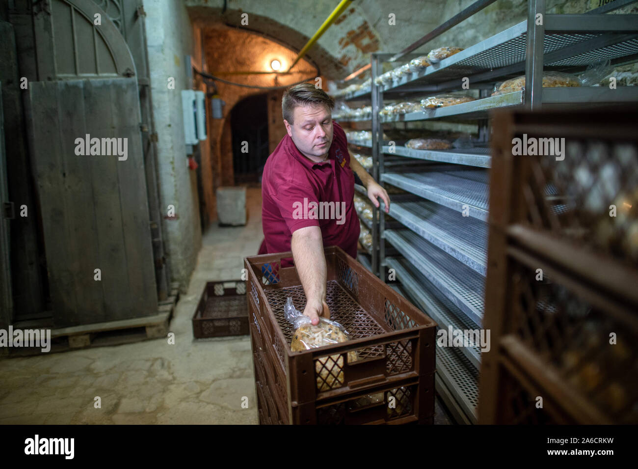 24 October 2019, Saxony-Anhalt, Halberstadt: Peter Potratz, master baker with the Halberstadt bakers and confectioners stores fresh Stollen in the Remter cellar of the cathedral. The bread-like cake covered with icing sugar is to be stored in the Remter cellar of the cathedral in the coming weeks and matured in the constant climate of the vault. The Halberstadt cathedral gallery will be cut on 30 November 2019 in the cathedral during a devotion. Photo: Klaus-Dietmar Gabbert/dpa-Zentralbild/ZB Stock Photo