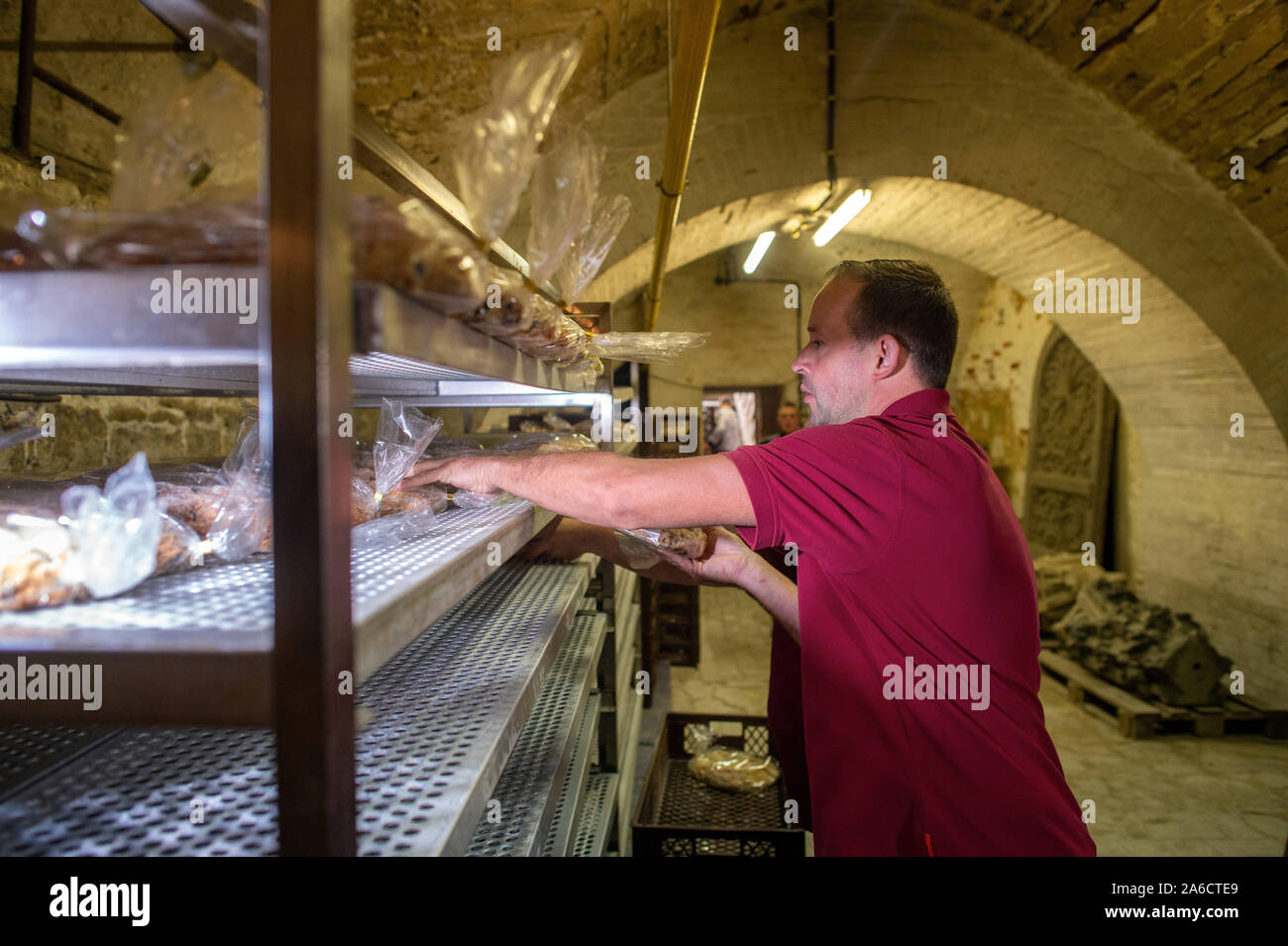 24 October 2019, Saxony-Anhalt, Halberstadt: Mathias Hlady, baker at the Halberstädter Bäcker und Konditoren, puts fresh Stollen into a steel shelf in the Remterkeller of the cathedral. The bread-like cake covered with icing sugar is to be stored in the Remter cellar of the cathedral in the coming weeks and matured in the constant climate of the vault. The Halberstadt cathedral gallery will be cut on 30 November 2019 in the cathedral during a devotion. Photo: Klaus-Dietmar Gabbert/dpa-Zentralbild/ZB Stock Photo