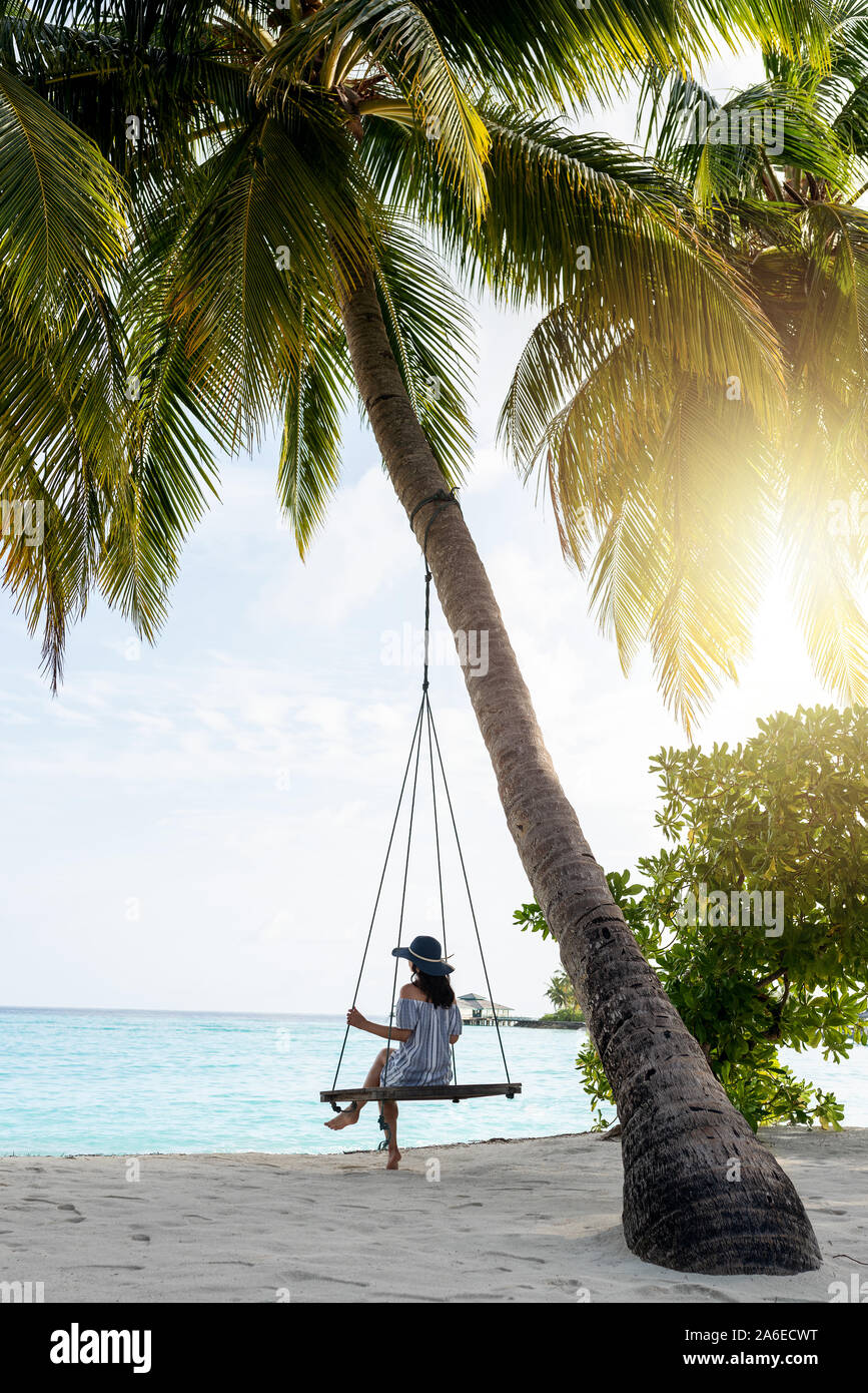 Young beautiful woman relaxing in swing hanging on coconut palm at exotic beach. Blue sea and white sand. Fashion girl enjoying on seashore. Portrait Stock Photo