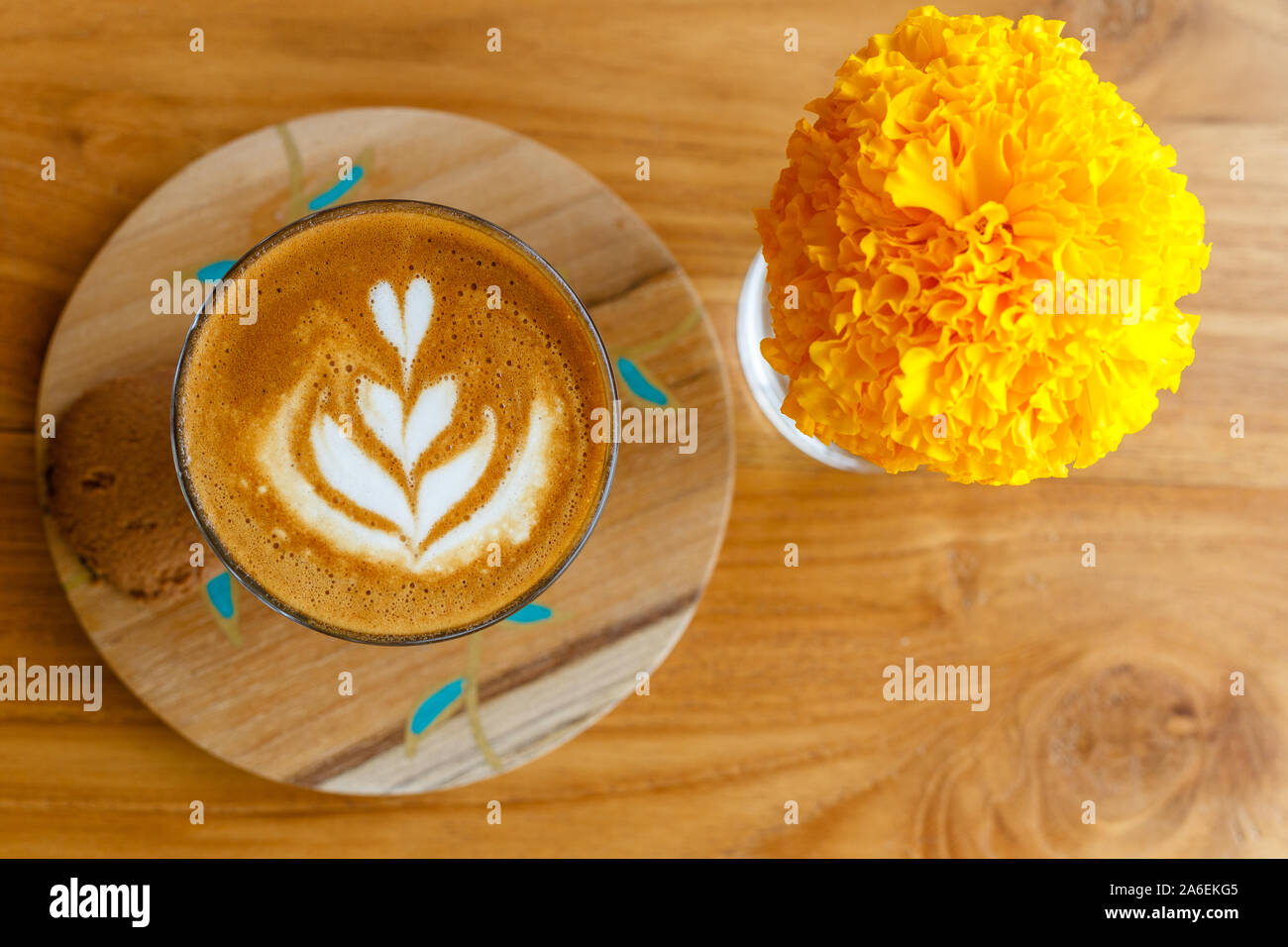 Cup of coffee piccolo in a wooden holder over wooden table in a cafe. Marigold flower in a glass. Top view. With space. Stock Photo