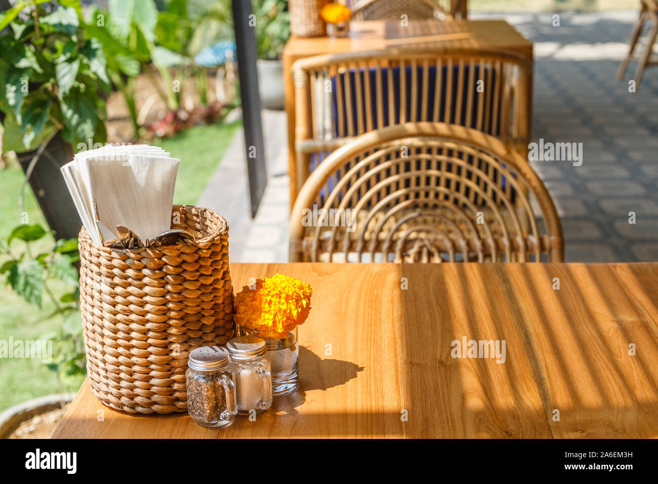 Natural color wooden and rattan furniture at an outdoor cafe. Blue cushions, fresh Marigold flowers, thatched tissue holders. Sunny morning. Stock Photo