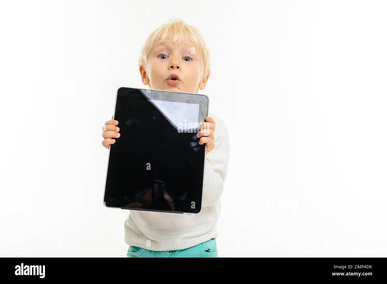 Little Boy With Short Blonde Hair Blue Eyes Cute Appearance In White Jacket Light Blue Pants Stands With A Tablet And Holds It In His Hands Stock Photo Alamy
